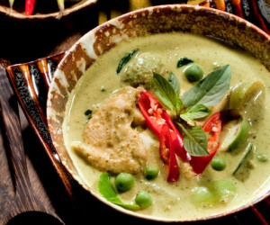 A bowl of traditional Thai green curry served with Thai eggplant and eggplant peas.